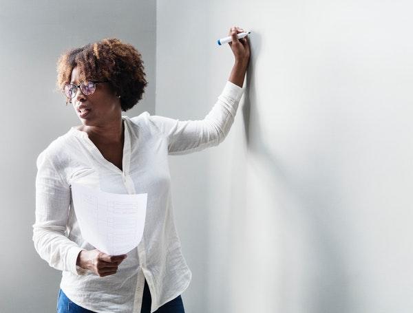 Lady teacher writing in white board